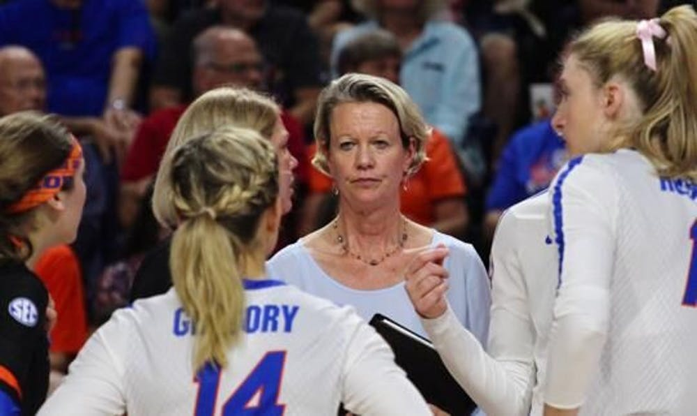 <p>Florida volleyball coach Mary Wise stands with her team in a huddle.</p>