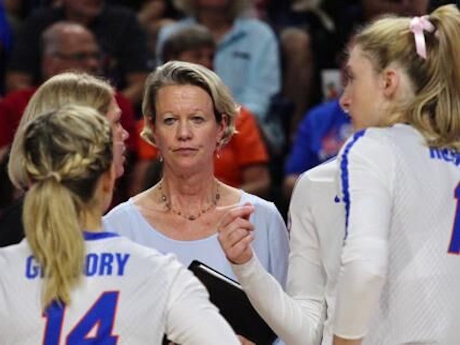 Florida volleyball coach Mary Wise stands with her team in a huddle.