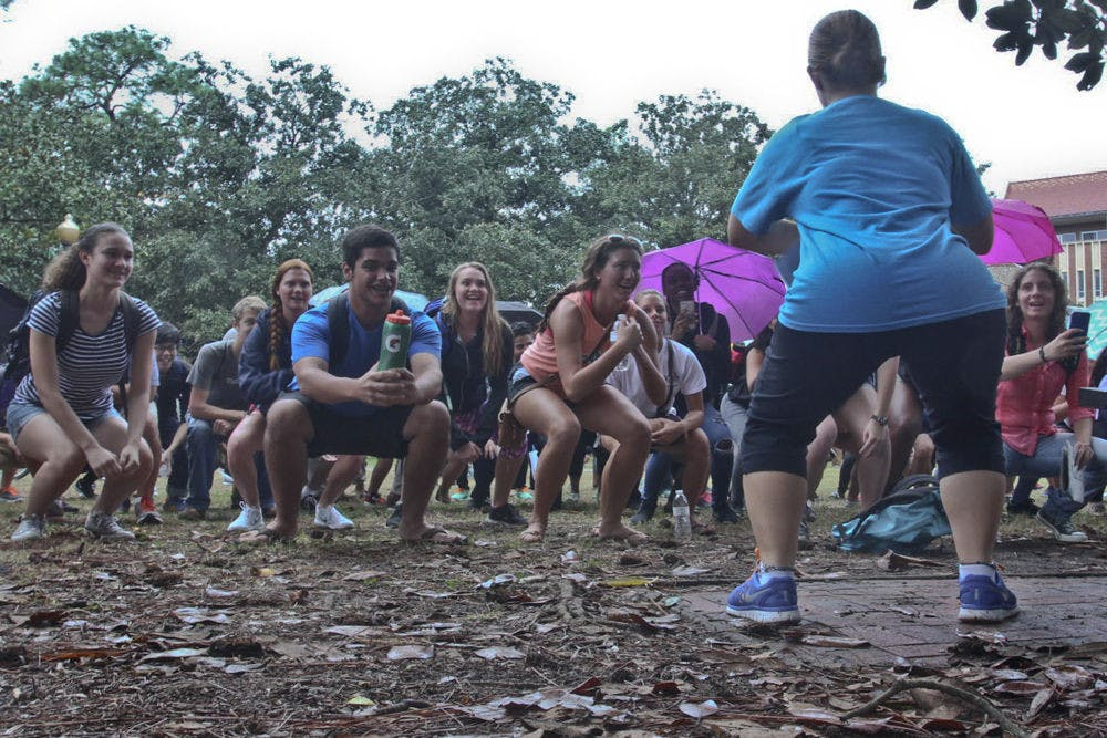 <p>Jodi Bieluch (right), a 20-year-old psychology junior, leads a group of about 80 students to squat in an attempt to break a world record on the Plaza of the Americas on Nov. 19, 2015. Gators for UNICEF hosted the squat to inform students about the 2.5 million people around the world who don't have access to restrooms.</p>