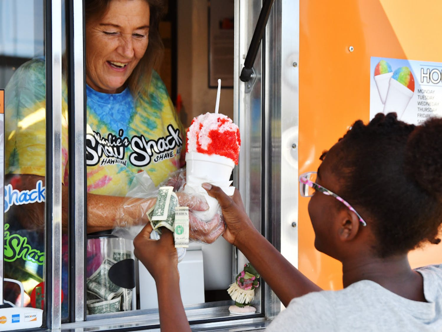 Linda Smith hands Kalani Breen, 11, a shaved ice cup in exchange for $3.50. Breen ordered a cherry-and-cotton-candy shaved ice with marshmallow topping, one of Charlie's sweeter dessert options.