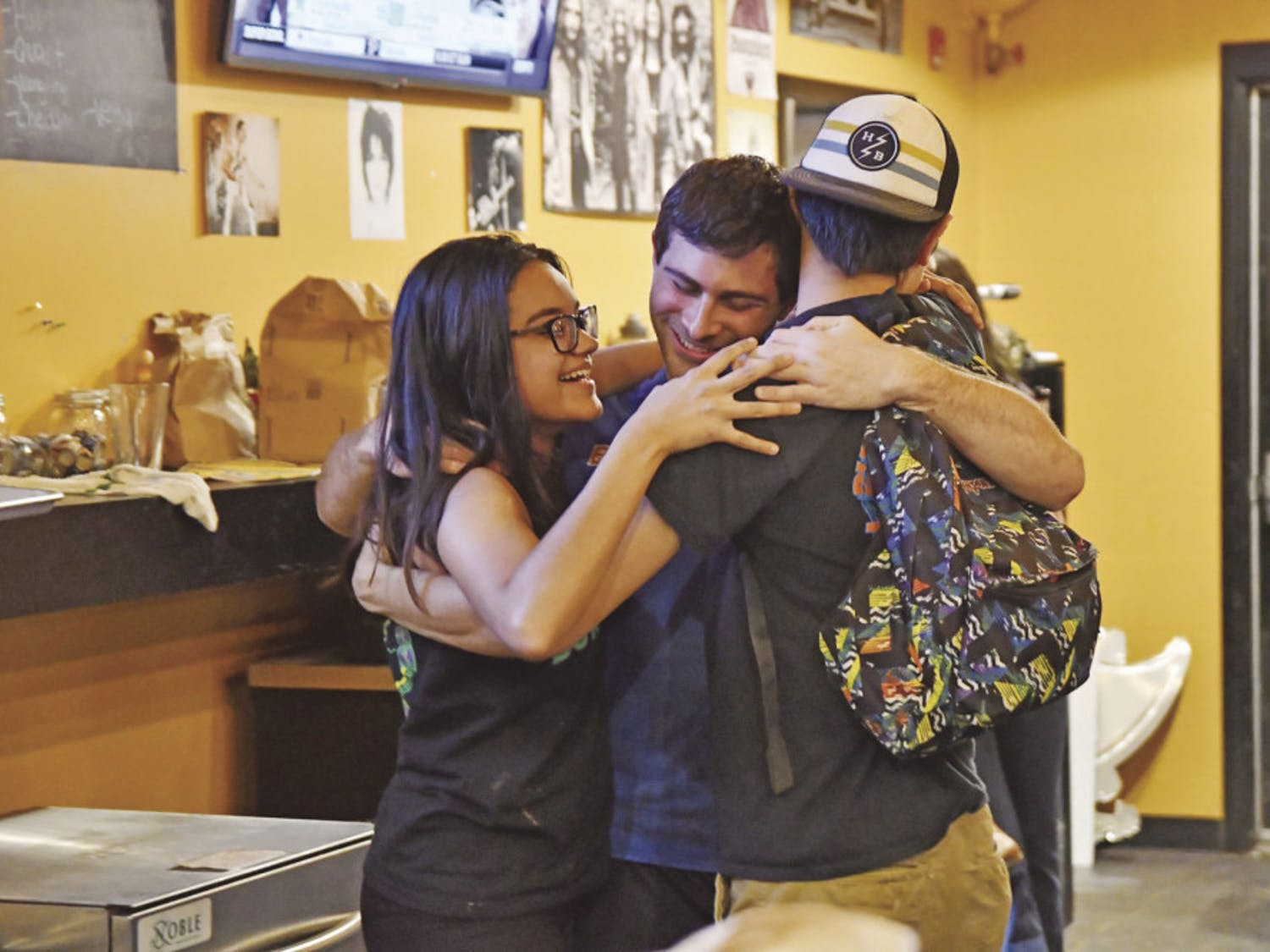 From left: Karla Arboleda, a 20-year-old UF journalism junior, Chase Dryer, a 22-year-old UF telecommunication senior, and William McDavid, a 19-year-old Santa Fe College pre-nursing sophomore, hug on Saturday evening.