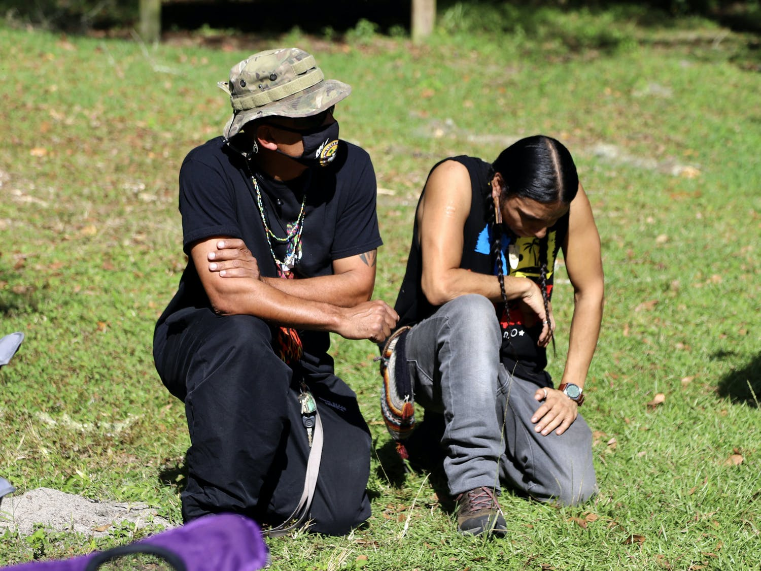 Robert Rosa (left), 52, a member of the Borinquen Taino nation and Stuart Flores (right), a member of the Algonquin Maya nation, kneel together, during the protest, in honor of their ancestors on Thursday, Dec. 3, 2020. The two explained that in Native American culture ancestors return to the soil after they pass away.