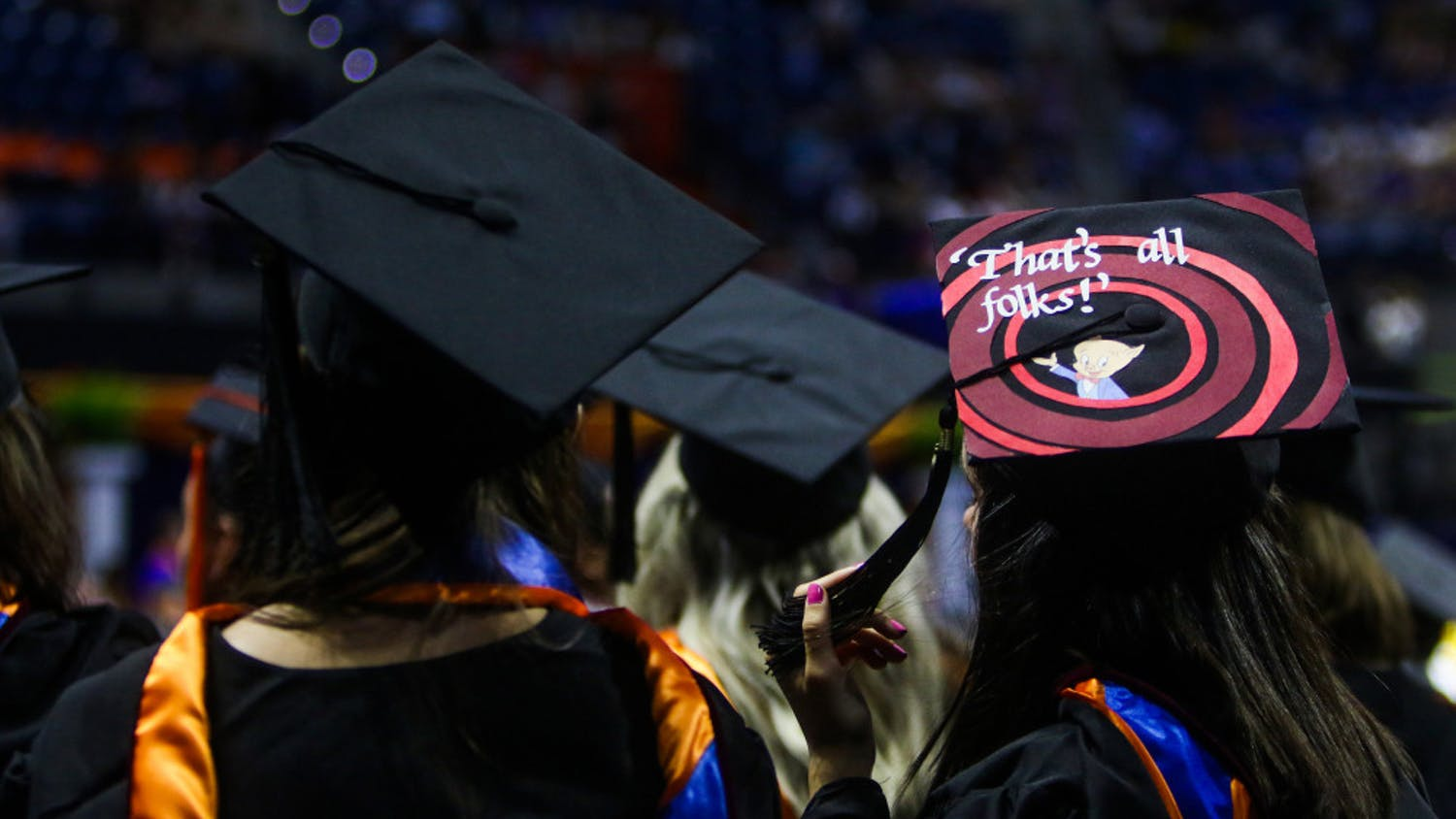 "A new graduate of the University of Florida watches the remainder of the ceremony while wearing a graduation cap with the Porky Pig quote, ""That's all, folks,"" from Looney Tunes."
