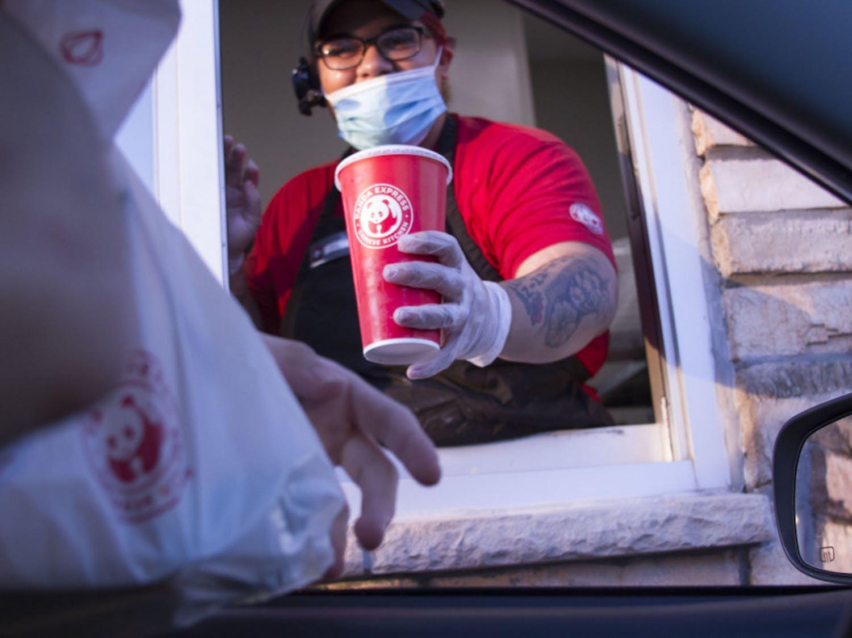 Kya Johnson, 19, passes food to a drive-thru customer.