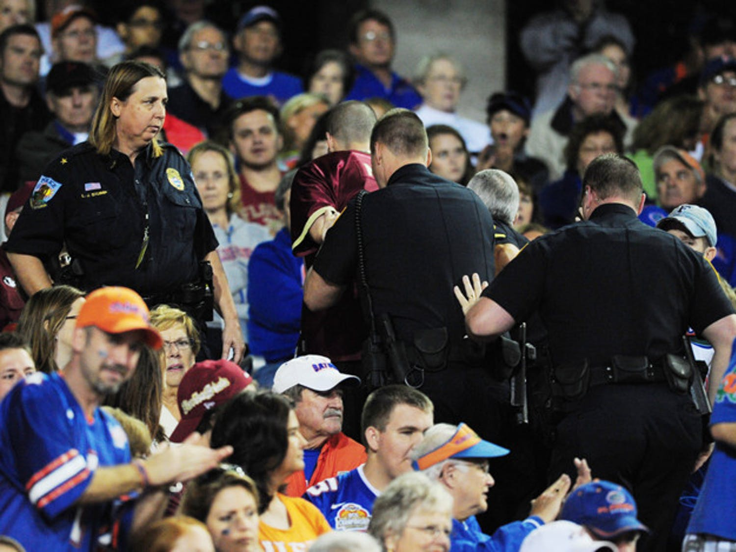 An FSU fan is handcuffed and escorted out of Ben Hill Griffin Stadium during Saturday's game.