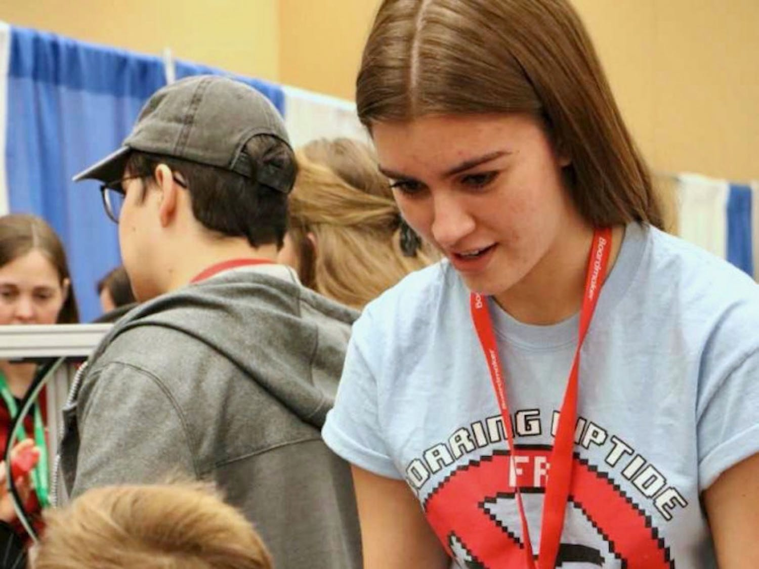 A student from P.K. Yonge Developmental Research School's First Robotics Club, 12th-grader Rebecca Schlafke, demonstrates how to use the club's adapted creations to a child at the Assistive Technology Industry Association Maker's Day on Saturday.