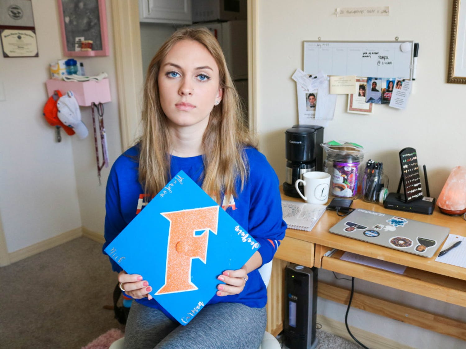 Elizabeth Stout, Parkland survivor and UF political science freshman, shows the cap she made for her graduation from Marjory Stoneman Douglas High School. Stout says she wants it to honor the four seniors that were unable to graduate due to the tragedy: Carmen Schentrup, Nicholas Dworet, Meadow Pollack and Joaquin Oliver.