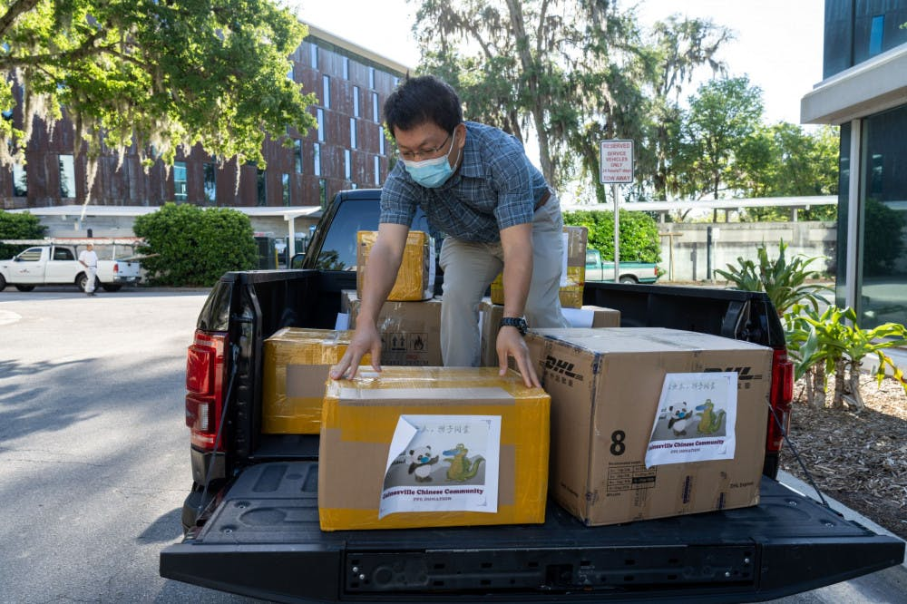 <p>Changweng Deng, one of the donation organizers, unloads boxes of PPE from the back of a pickup truck on Thursday to donate to UF Health Shands Hospital. Everyone present at the donation observed social distancing guidelines by standing six feet apart and wearing facemasks to protect themselves from COVID-19, they told The Alligator.</p>