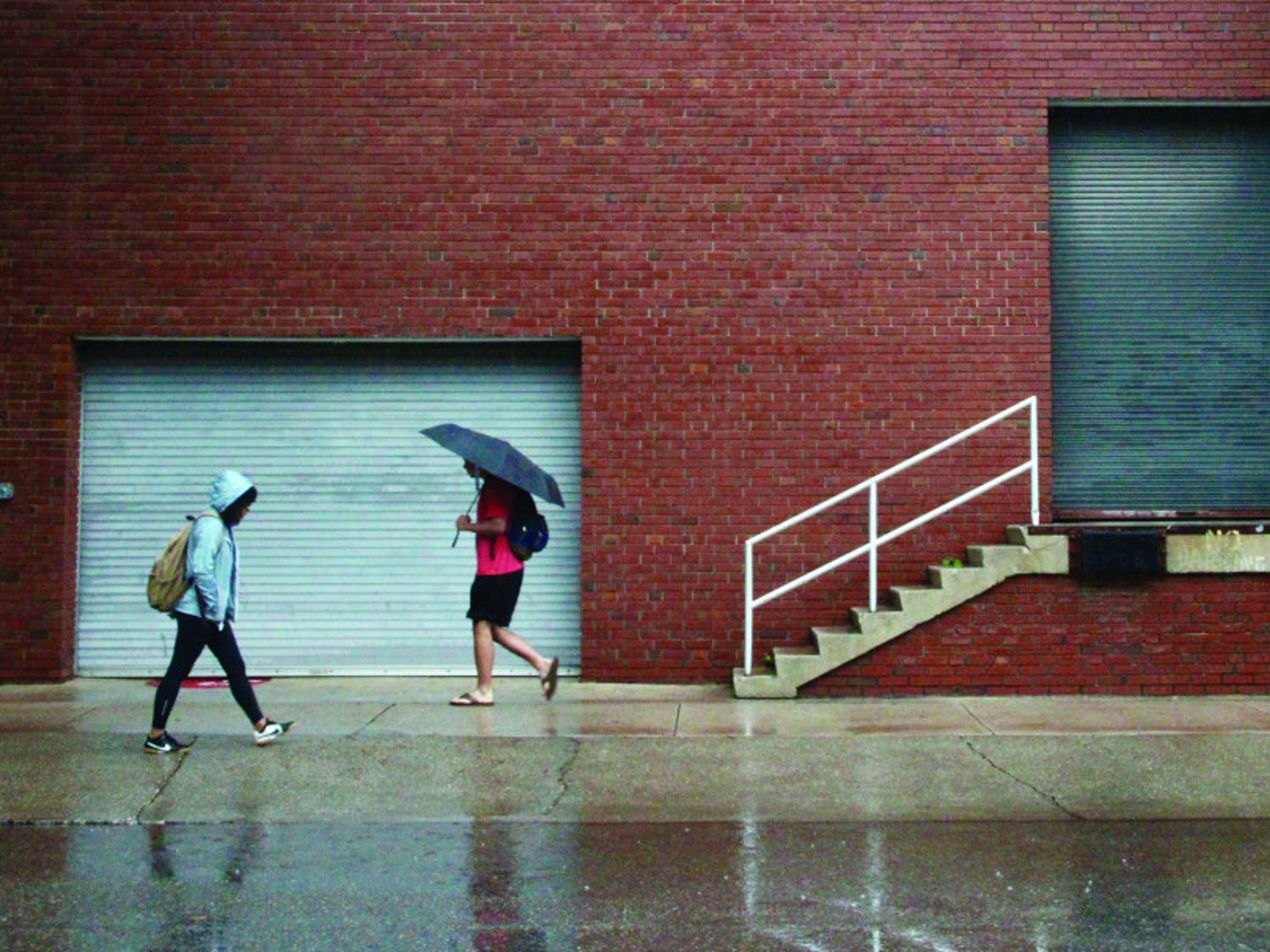 Students walk to class in rainy weather.