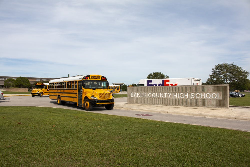 <p>In this Oct. 17, 2019 photo, buses depart from Baker County High School in Glen St. Mary, Fla. Unease spread across Baker County when authorities arrested a 15-year-old who they say planned a massacre at the county's only high school. Anger grew when a judge dismissed second-degree felony charges against the boy.(AP Photo/Bobby Caina Calvan)</p>