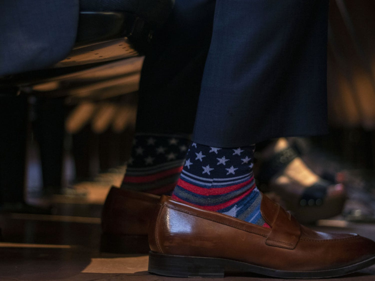 Senator Keith Perry wears socks with stars and stripes Thursday while waiting for Donald Trump Jr. to speak.