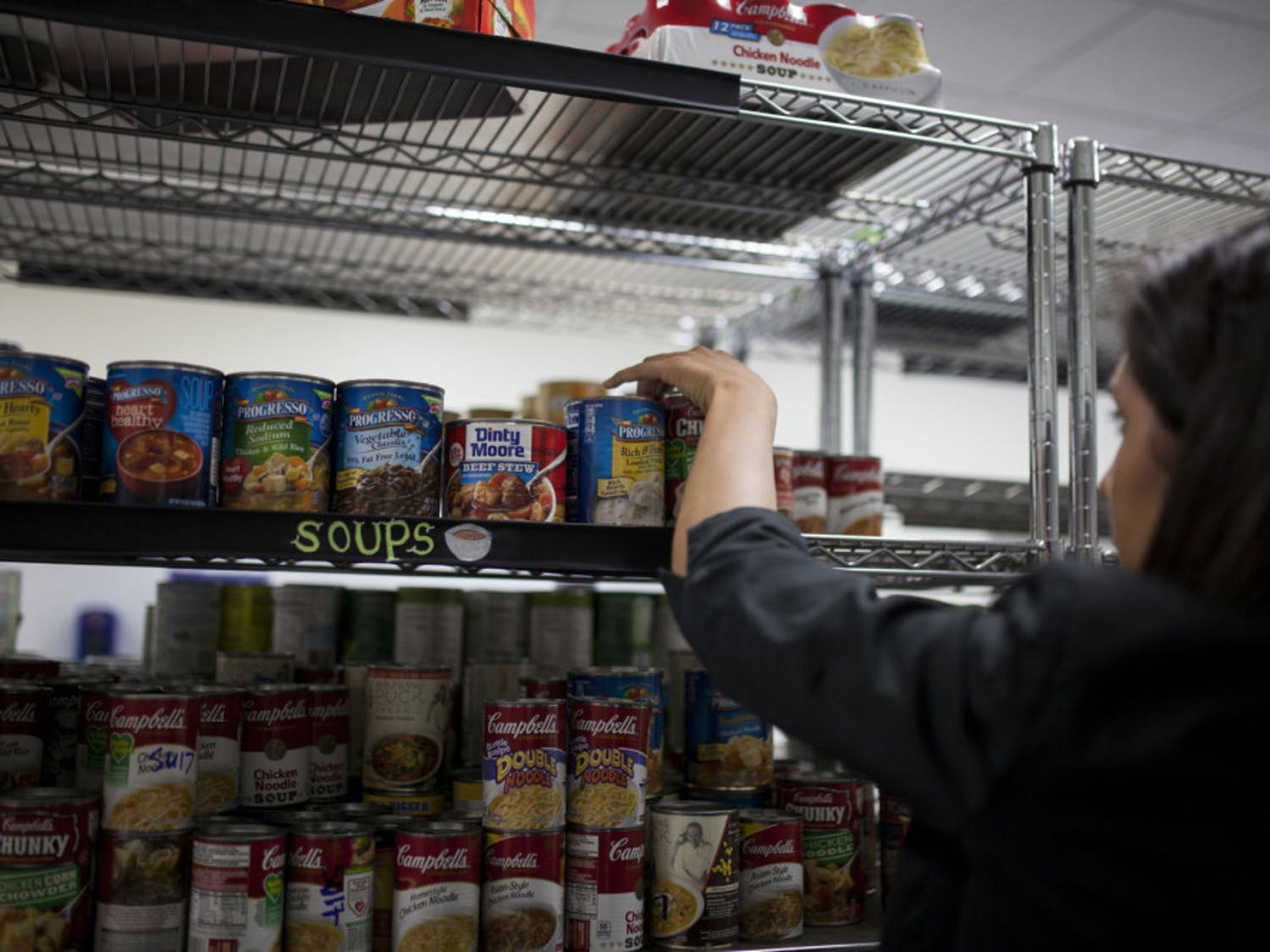 A volunteer stocking shelves with canned food at the Field and Fork Pantry on UF's campus in 2016.