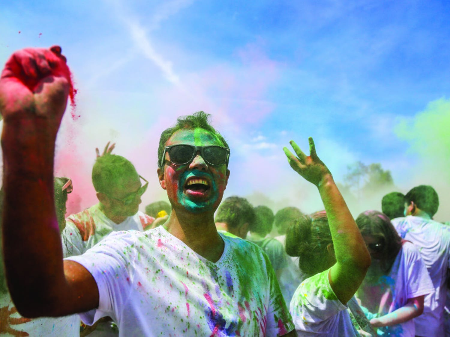 Khem B. Banjara, a 30-year-old neuro technologist at UF Health Shands Cancer Hospital, throws paint during the UF Holi Festival of Colors, organized by the UF Indian Student Association and Student Government, on Sunday afternoon. Above, more than 1,000 people attended the event, which lasted more than three hours.
