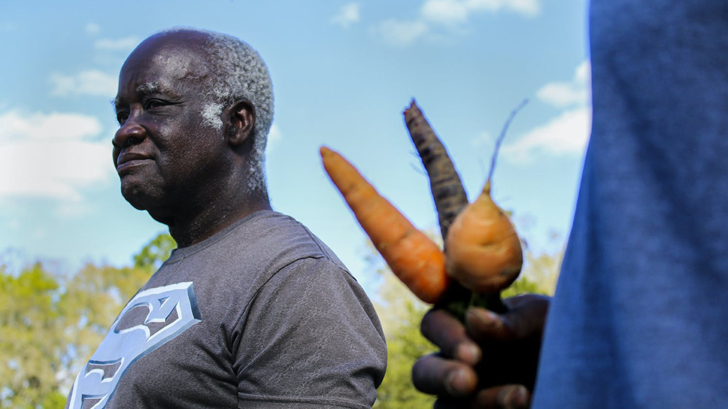 Lennon Fisher Jr. holds three different kinds of carrots in his hand while Lennon Fisher looks at the field. They said some of their favorite produce are their carrots.