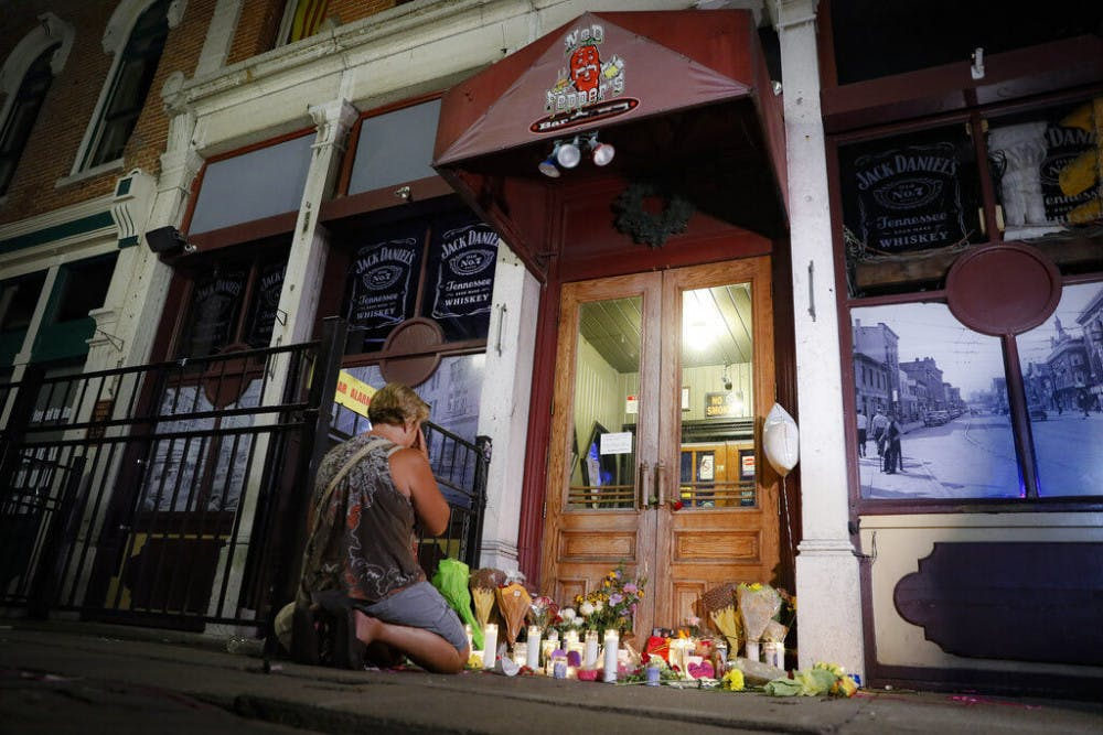 <p>Mourners visit a makeshift memorial outside Ned Peppers bar following a vigil at the scene of a mass shooting, Sunday, Aug. 4, 2019, in Dayton, Ohio. A masked gunman in body armor opened fire early Sunday in the popular entertainment district in Dayton, killing several people, including his sister, and wounding dozens before he was quickly slain by police, officials said.&nbsp;</p>