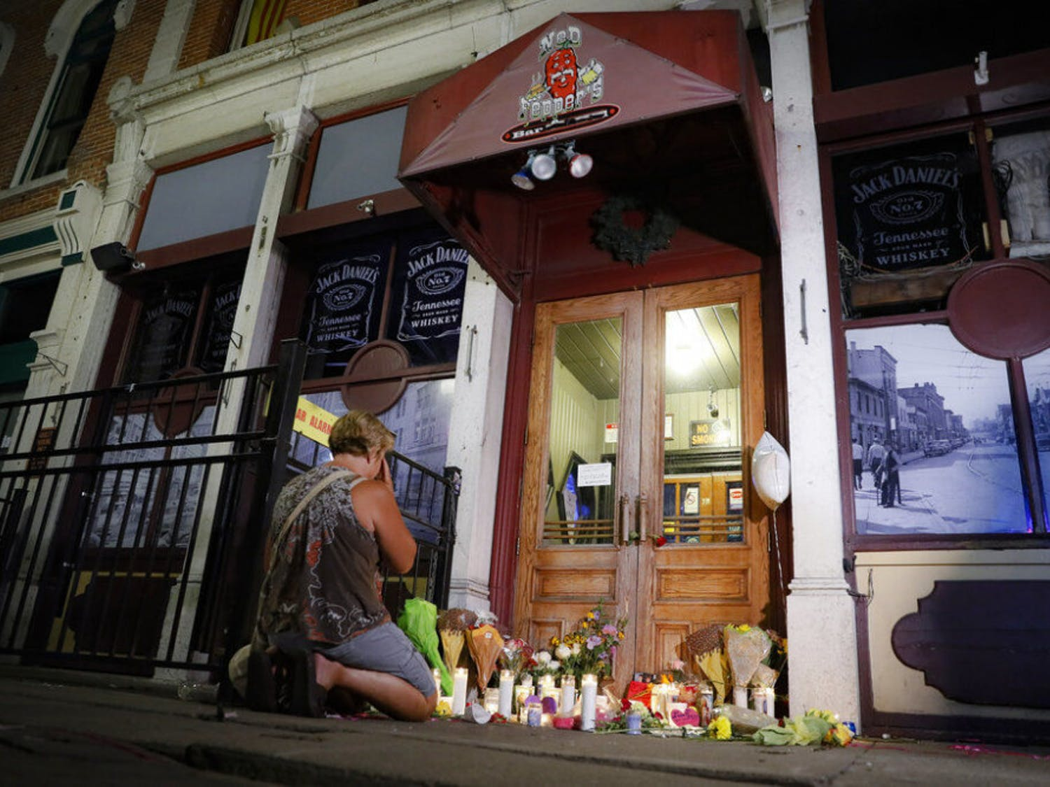 Mourners visit a makeshift memorial outside Ned Peppers bar following a vigil at the scene of a mass shooting, Sunday, Aug. 4, 2019, in Dayton, Ohio. A masked gunman in body armor opened fire early Sunday in the popular entertainment district in Dayton, killing several people, including his sister, and wounding dozens before he was quickly slain by police, officials said.