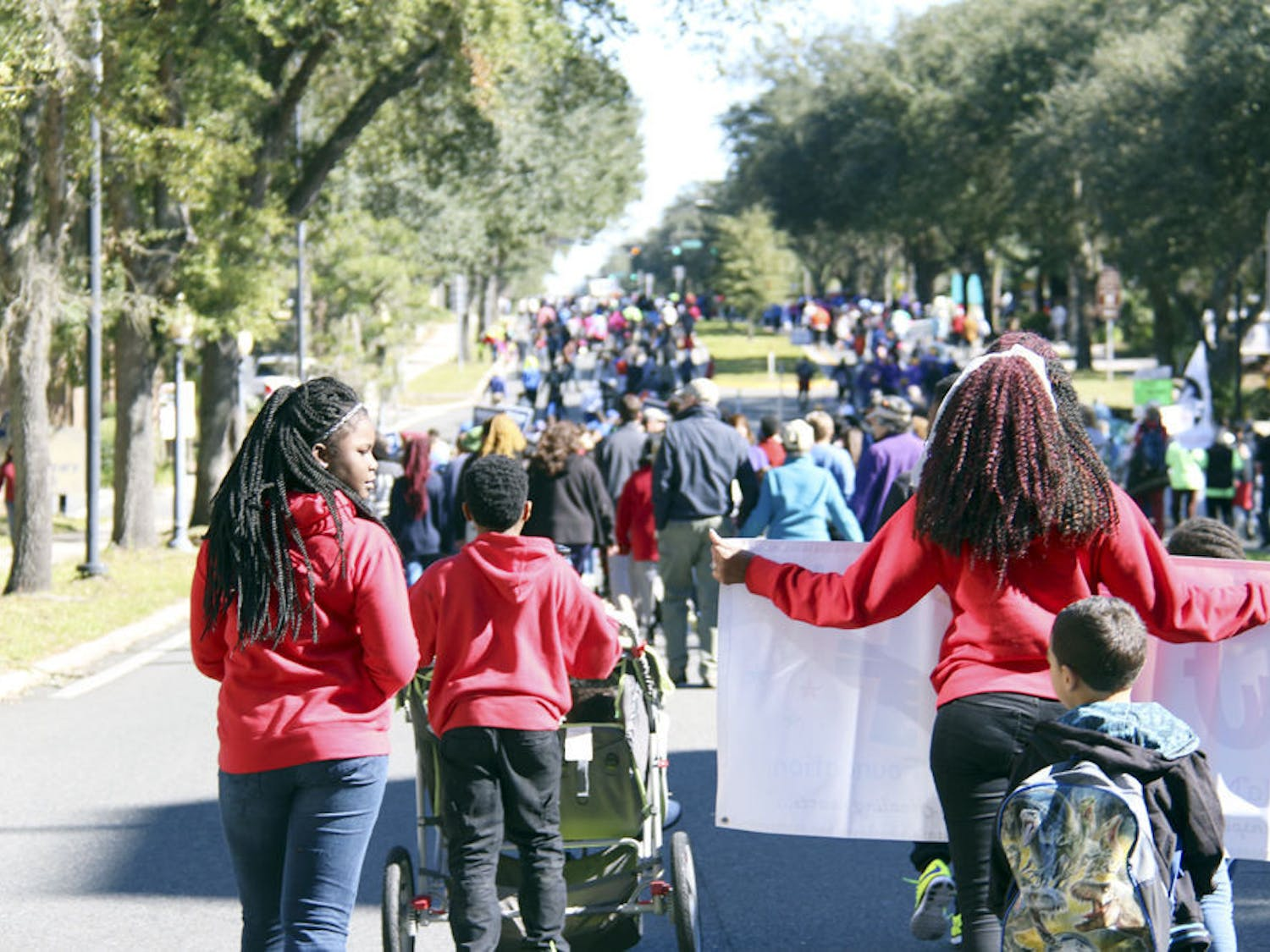 Hundreds of people showed their support for Martin Luther King Jr. and the equality for which he stood by walking east down University Avenue on Jan. 18, 2016. Some held signs for other causes they supported, such as stricter gun laws or mayoral candidates in Gainesville, while others walked with friends from church and sang impromptu, uplifting songs along the way.
