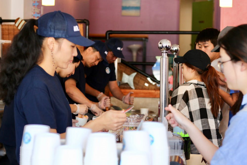 """<p dir=""""ltr""""><span>Mr. Cool Ice Cream employees serve rolled ice cream to customers at its Grand Opening event on Thursday. The line was out the door on Saturday evening.</span></p><p><span></span></p>"""