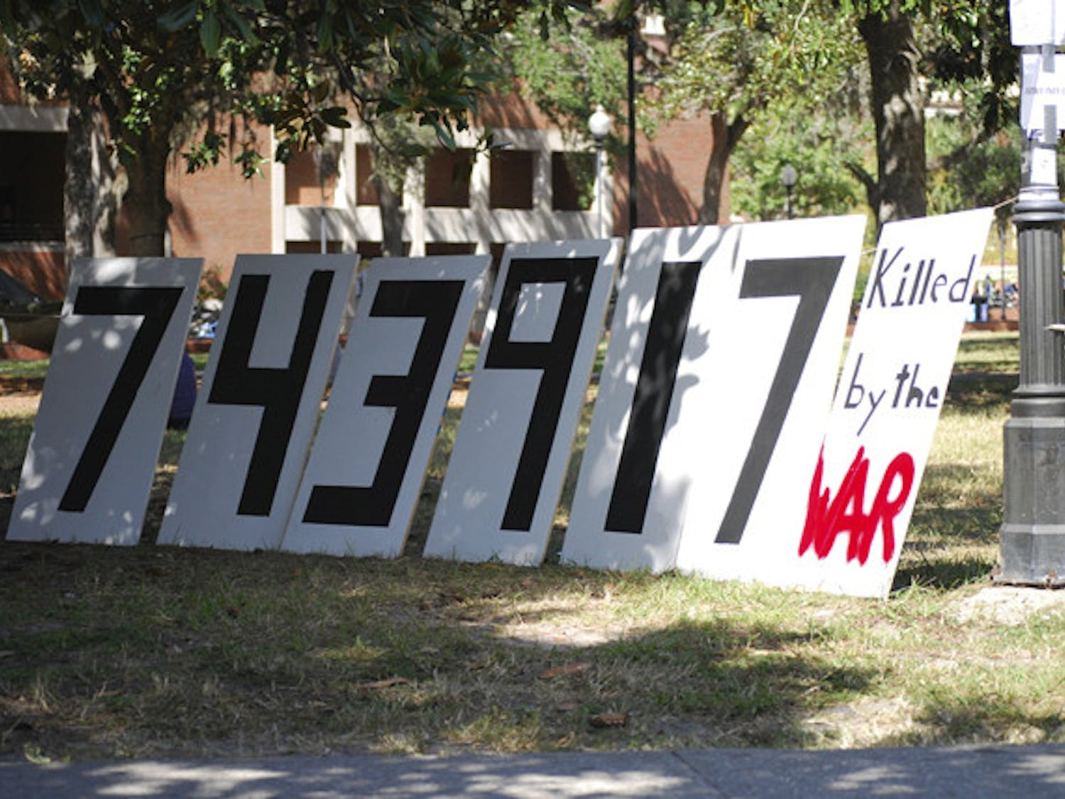"""A sign that reads """"743,917 killed by the war"""" sits on the Plaza of the Americas at a protest on Friday against the wars in Afghanistan and Iraq."""
