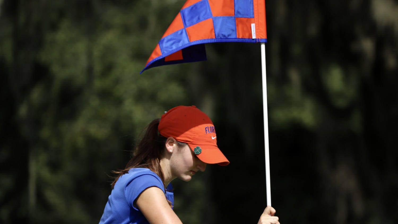 Freshman Maisie Filler adjusts a flag at Mark Bostick Golf Course.