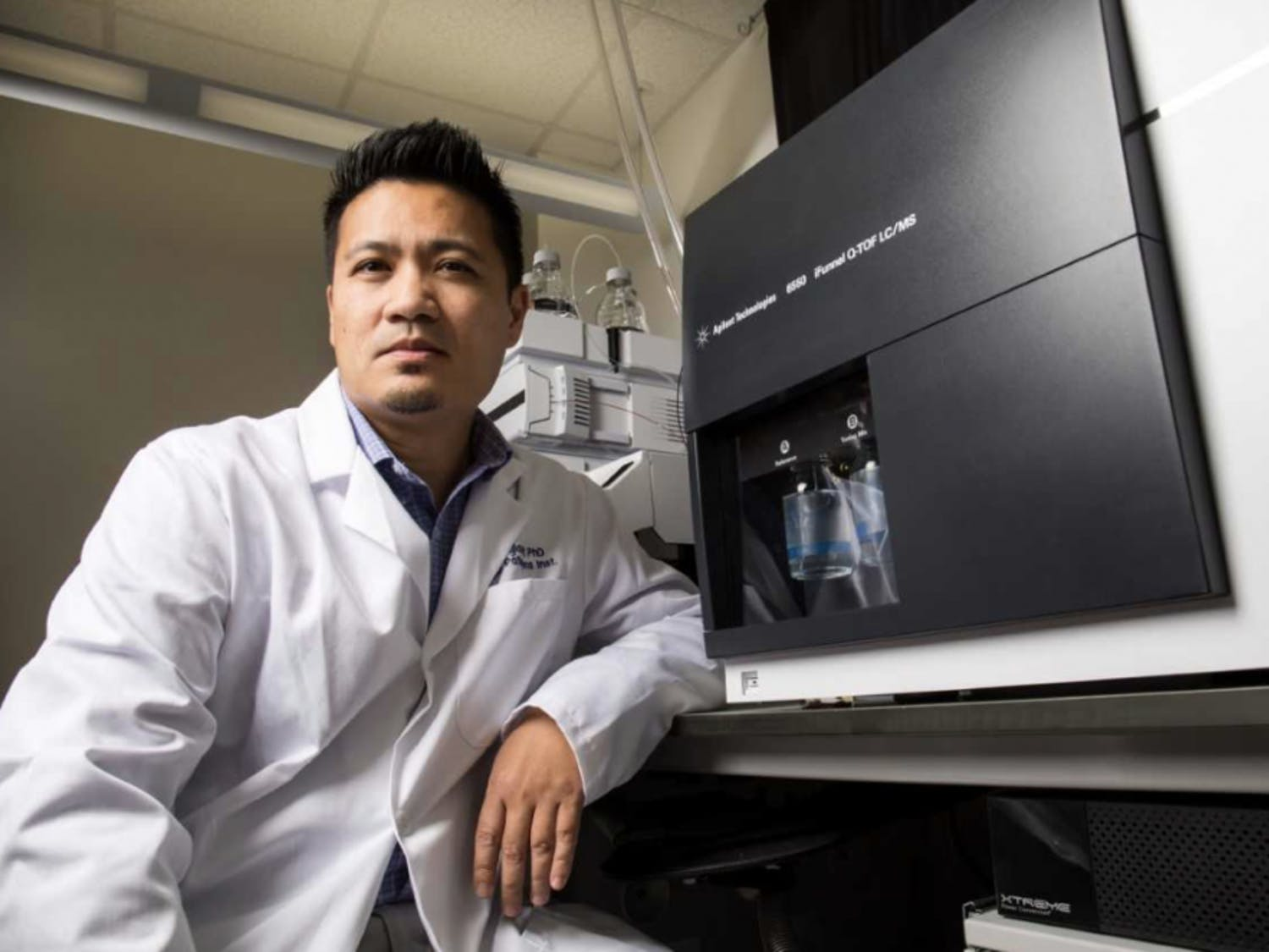 Rhoel Dinglasan, UF associate professor of infectious diseases and leader of the project which developed the Saliva-based Malaria Asymptomatic Asexual Rapid Test device, sits next to one of his agilent mass spectrometers which was used to gather data. Courtesy to The Alligator.