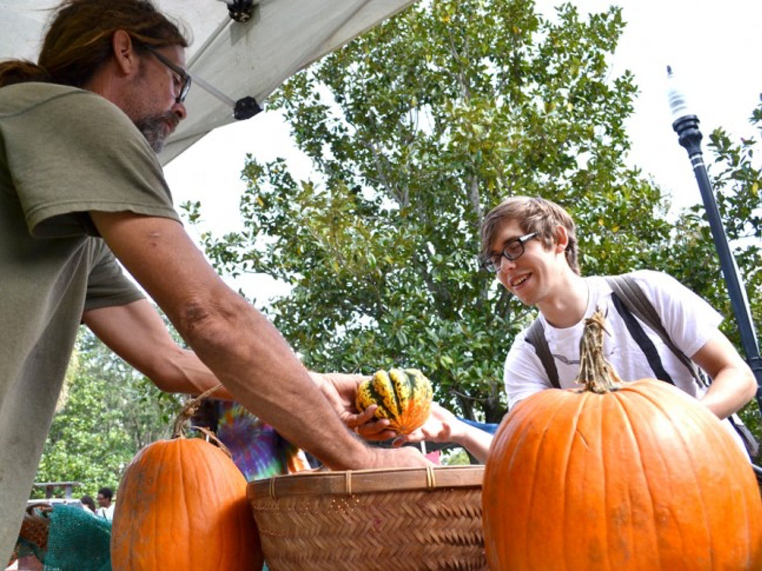 Magnolia Farms vendor Mike McElwee, 45, sells a squash to Jeremy Outinen, a 21-year-old anthropology senior, on Thursday at the Inter-Residence Hall Association's Farmers Market.
