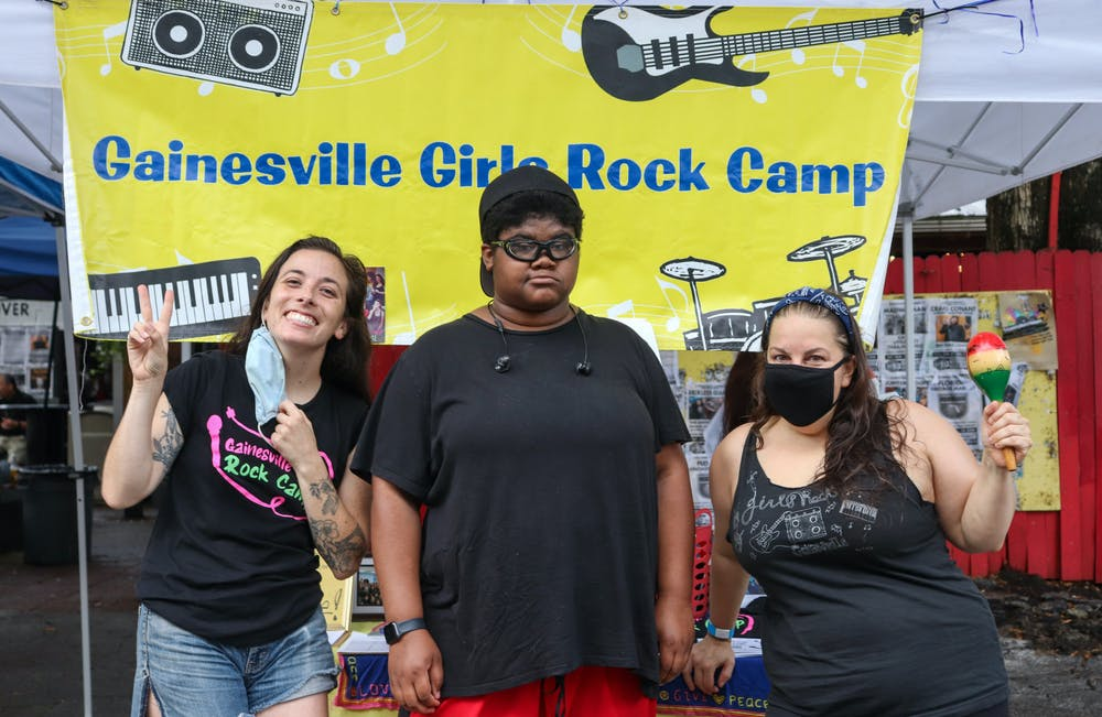 (Left to right) Coral Smith, Charlotte Katz Howick and Jennifer Vito stood in front of the information booth on Saturday. Howick was a previous camper of Gainesville Girls Rock Camp.