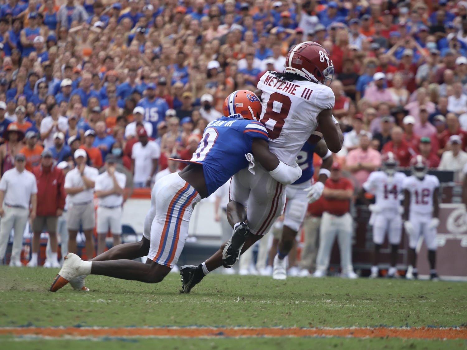 Safety Trey Dean III, pictured in blue, tackles Alabama wide receiver John Metchie III after he makes a catch.