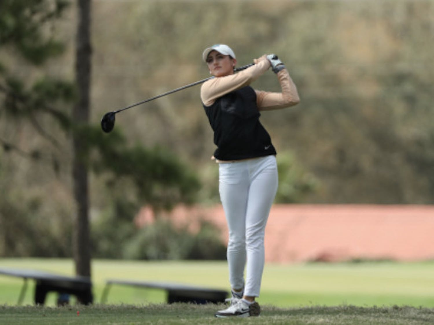 Maisie Filler watches her drive in February at the Gators Invitational