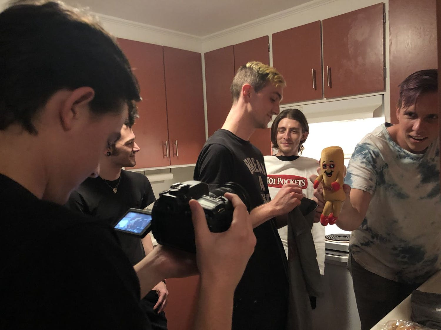 Behind the scenes of Arrows in Action's Hot Pockets unboxing video. The band's manager, Jacob McKay, films bassist Tony Farah, guitarist Matt Fowler, lead vocalist Victor Viramontes-Pattison and drummer Jesse Frimmel (from left to right).