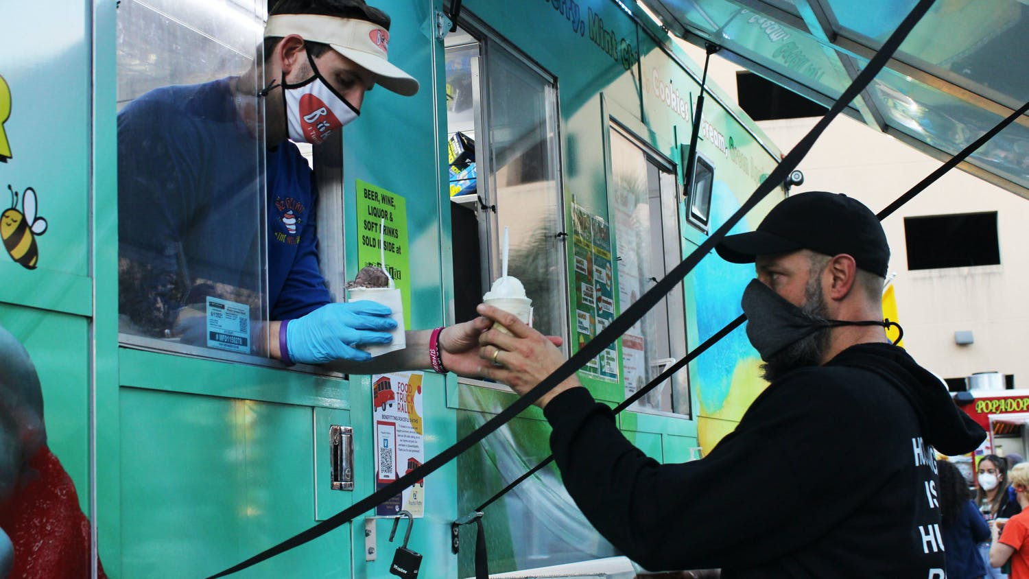 Gainesville resident Jon DeCarmine, 42, picks up gelato from the BZ Gelati Food Truck at the Original Gainesville Food Truck Rally hosted by High Dive on Saturday, Jan. 30, 2021.
