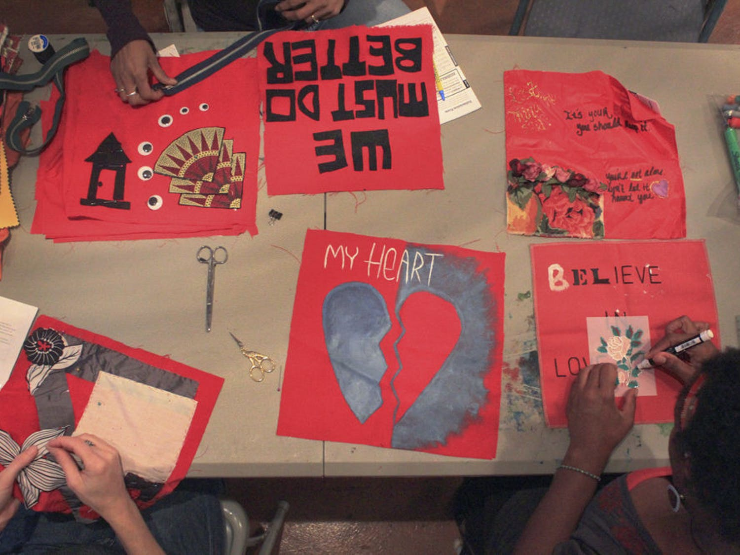 Sexual assault survivors came together to quilt their stories Oct. 19, 2015, at Wild Iris Books, a feminist bookstore at 22 SE 5th Ave. The evening was the last of three monthly workshops at Wild Iris where participants created squares for the Monument Quilt, a project that collects stories from rape and abuse survivors on red fabric squares and displays them in public spaces around the U.S.