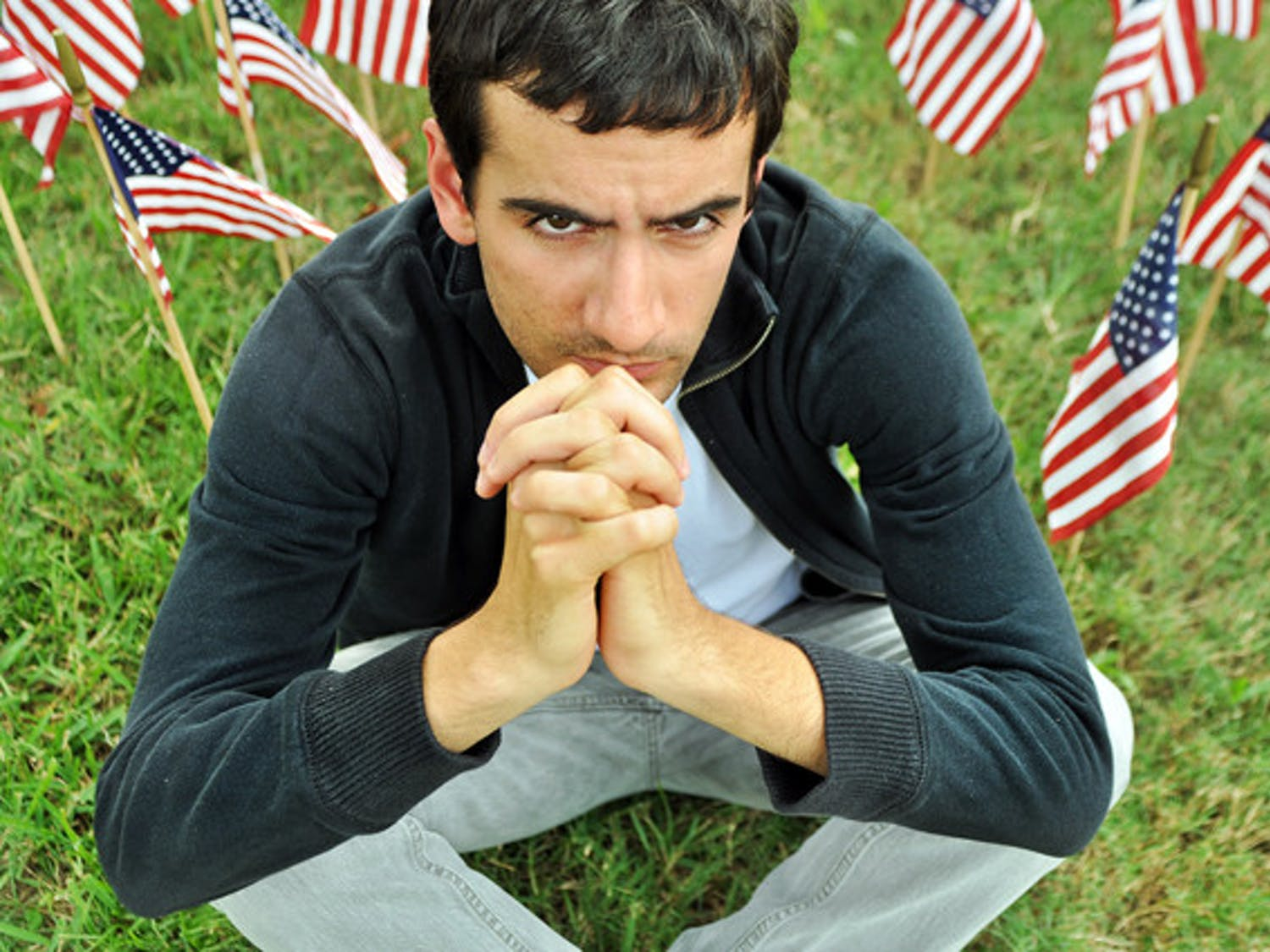 UF English senior Thomas Panevino, 21, who lived one block from the World Trade Center at the time of the 9/11 attacks, sits among the flags of the 9/11: Never Forget Project on the Reitz Union North Lawn.