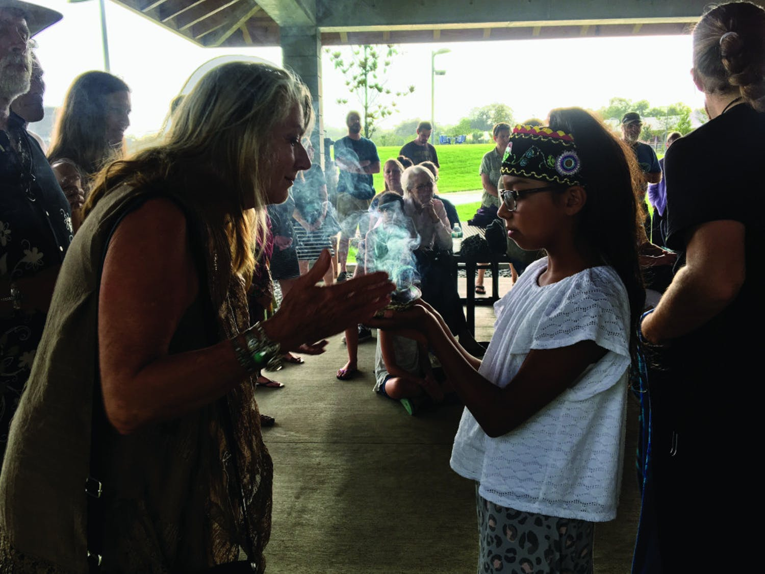 Lily Smith, 11, welcomed guests at a Wednesday night water ceremony held at Depot Park, located at 200 SE Depot Ave., by smudging them with sage. At the ceremony, about 30 people sang, danced and discussed the importance of the four elements — especially water.