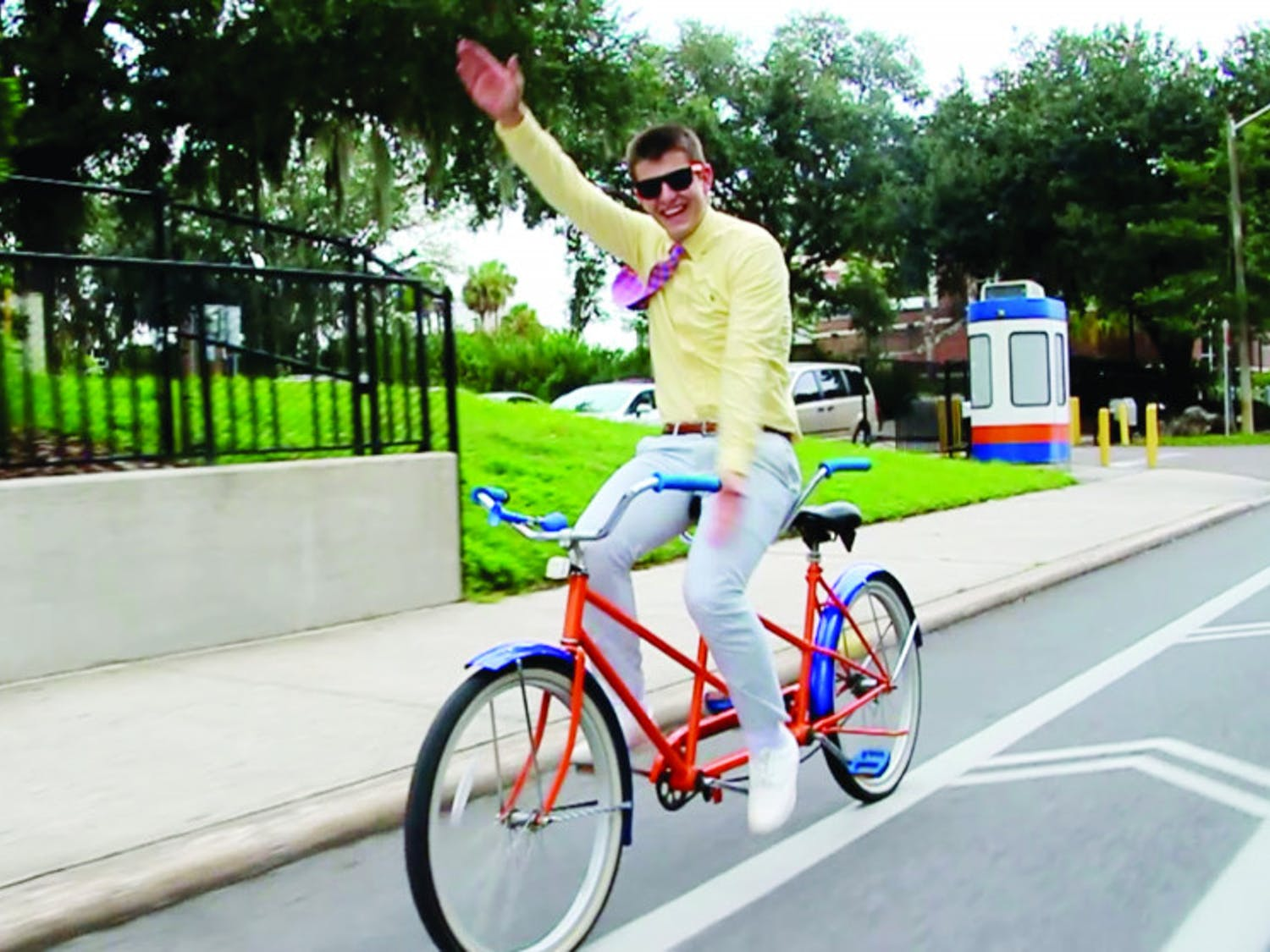Michael Cizek, a 19-year-old UF finance sophomore, Gator Chomps while bicycling down Stadium Road. He was chosen by the University Athletic Association as the winner of this year's Mr. Two Bits competition Monday.