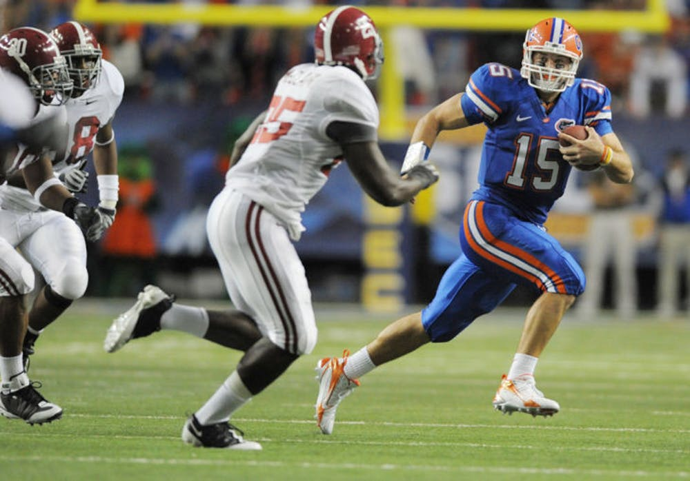 <p>Former Florida quarterback Tim Tebow (15) escapes pressure from Alabama linebacker Rolando McClain (25) during UF&#x27;s 31-20 win in the 2008 SEC Championship Game. Tebow signed with the Jaguars as a tight end May 20.</p>