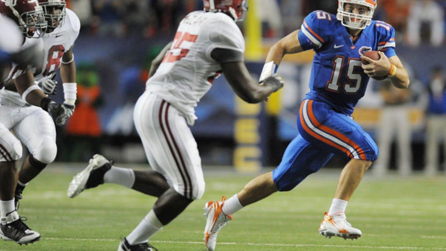 Former Florida quarterback Tim Tebow (15) escapes pressure from Alabama linebacker Rolando McClain (25) during UF's 31-20 win in the 2008 SEC Championship Game. Tebow signed with the Jaguars as a tight end May 20.