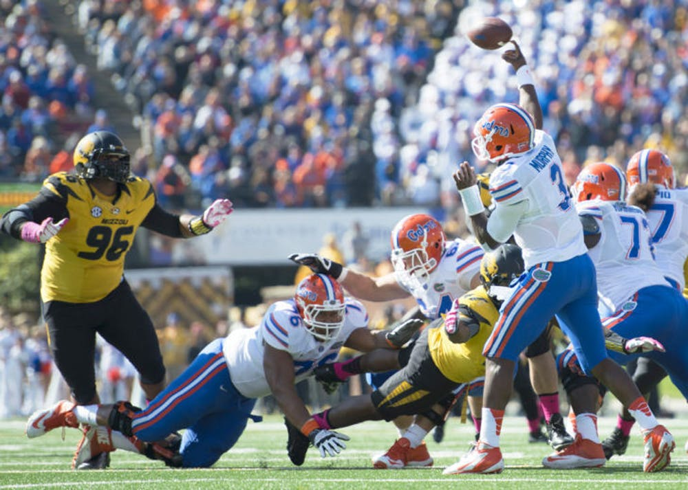<p>Max Garcia (76) lunges for a Missouri defender as redshirt junior quarterback Tyler Murphy (3) attempts a pass during Florida's 36-17 loss to Missouri on Oct. 19 at Faurot Field in Columbia, Mo. UF's line has allowed 10 sacks in the past two games.</p>
