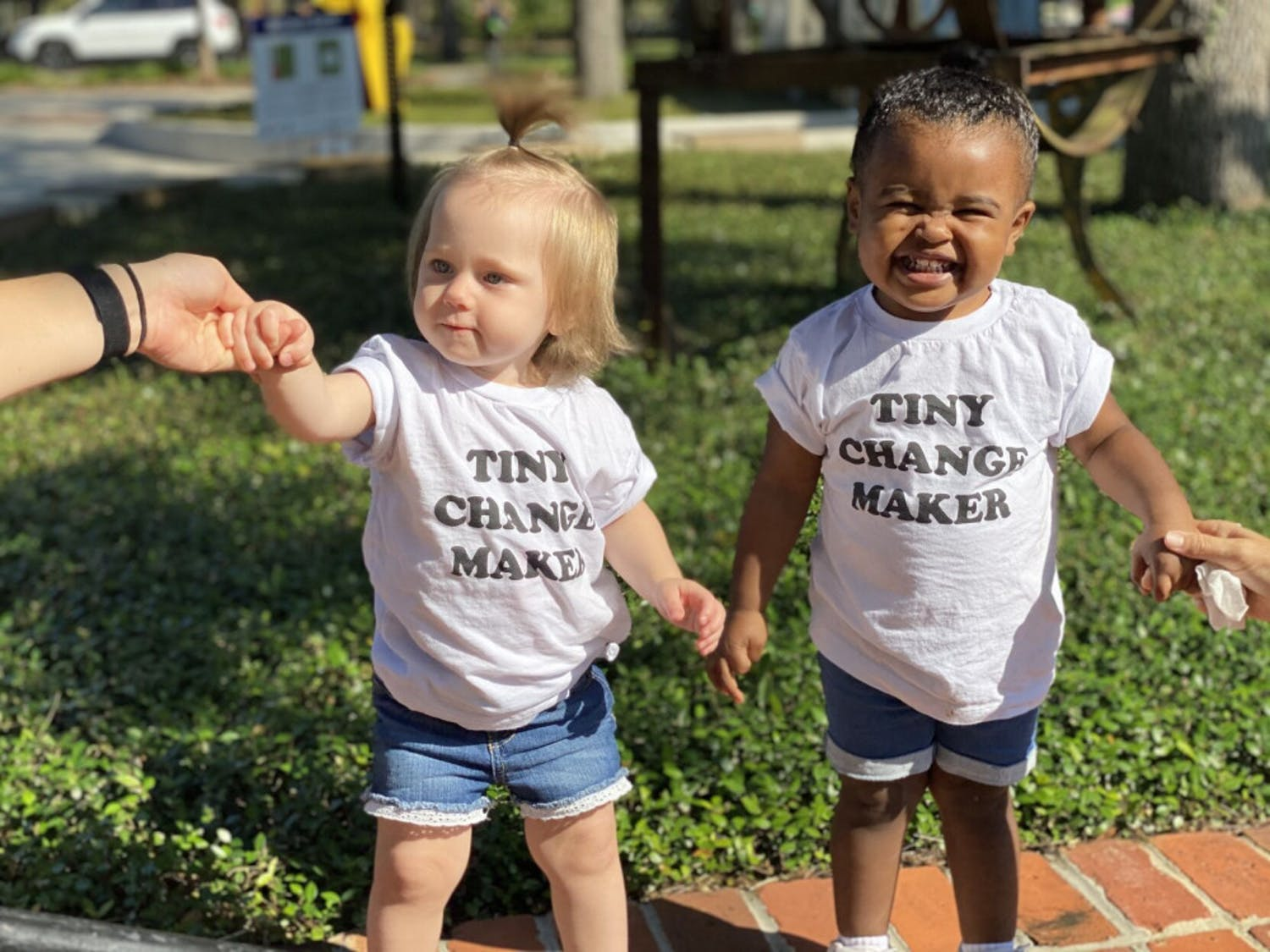 "Stevie VanAusdale, a 30-year-old UF PhD student and mental health professional who spoke at the rally, brought her two daughters, two-year-old Aria and one-year-old Maya whose shirts read ""Tiny Changemaker."""