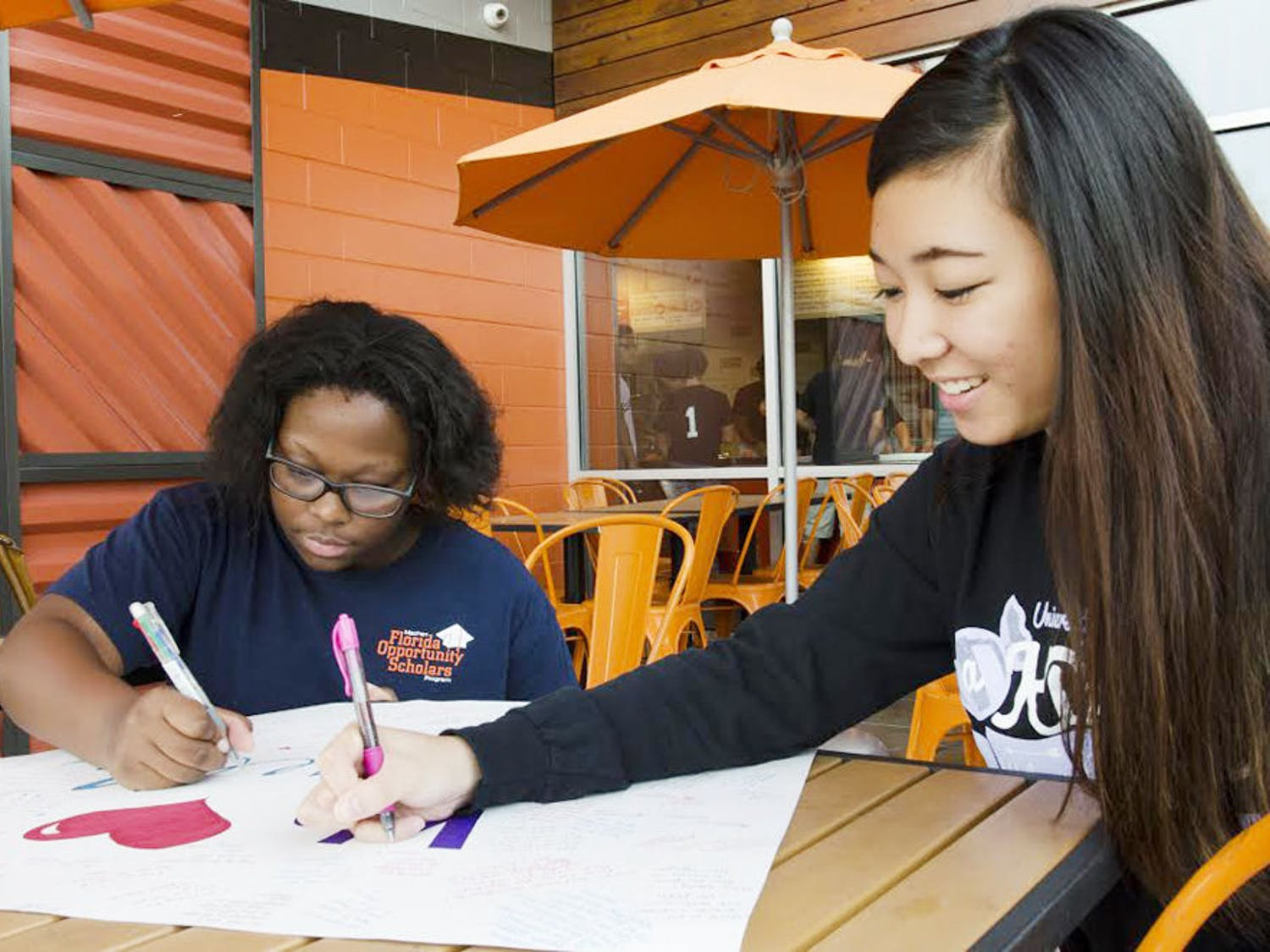 Kendra Phillip (left), 22-year-old UF health education graduate, and Athena Wong, 19-year-old UF accounting sophomore, sign a giant card for Roselle Derequito at Blaze Wednesday. Derequito's sorority, alpha Kappa Delta Phi, held a fundraiser to raise money for her medical expenses.