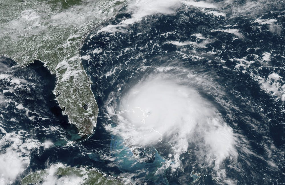 <p>This GOES-16 satellite image taken Sunday, Sept. 1, 2019, at 17:00 UTC and provided by National Oceanic and Atmospheric Administration (NOAA), shows Hurricane Dorian, right, churning over the Atlantic Ocean. Hurricane Dorian struck the northern Bahamas on Sunday as a catastrophic Category 5 storm, its 185 mph winds ripping off roofs and tearing down power lines as hundreds hunkered in schools, churches and other shelters. (NOAA via AP)</p>