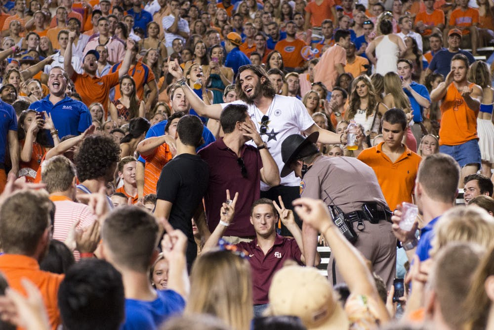 """<p class=""""p1"""">A man wearing a Florida State University shirt reacts prior to being escorted out by police in Ben Hill Griffin Stadium during halftime at the Kentucky game Saturday night.</p>"""