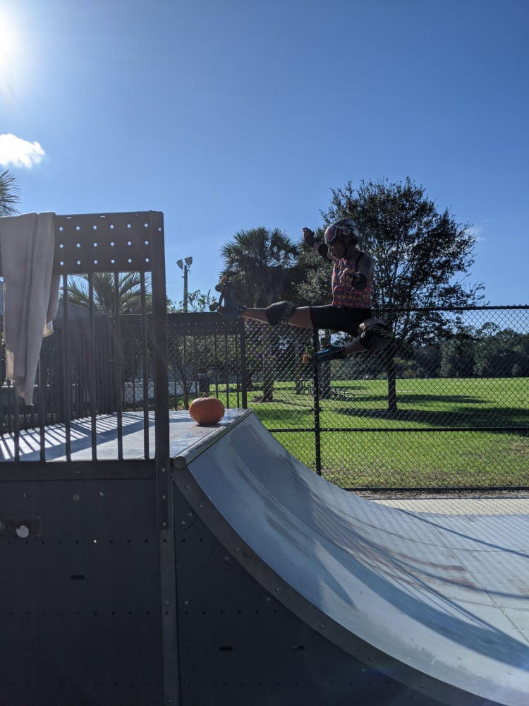 A member of the Roller Rebels leaping over a pumpkin