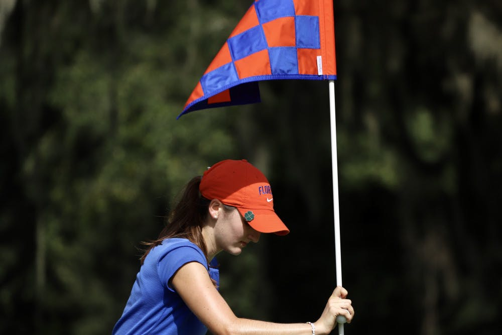 <p>Freshman Maisie Filler adjusts a flag at Mark Bostick Golf Course. She won her final match of the fall season Wednesday.</p>