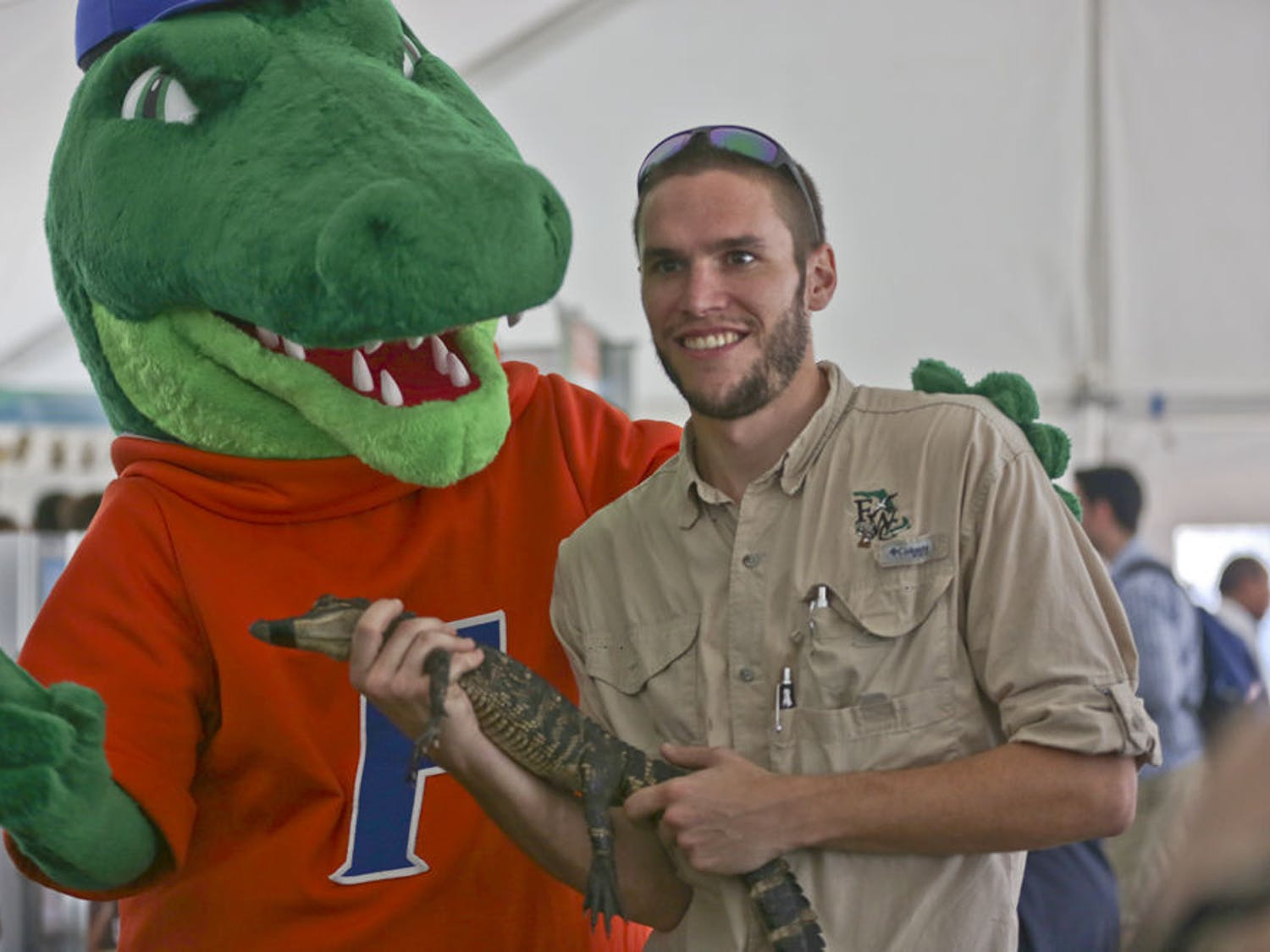Rob Cuskley, a 28-year-old biological scientist, introduces a baby american alligator to Albert during the campus showcase for Inauguration Week on Dec. 2, 2015. The Florida Museum of Natural History encouraged Cuskley to bring the alligator to educate students.