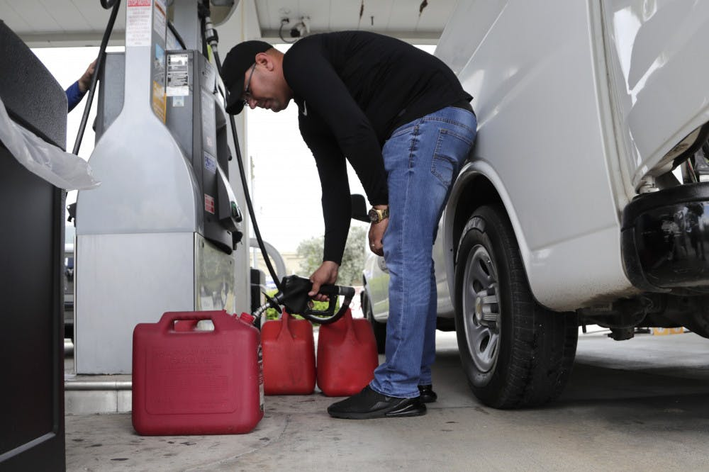 <p>Arian Britto fills containers with gasoline at BJ's Wholesale Club in preparation for Hurricane Dorian, Thursday, Aug. 29, 2019, in Hialeah, Fla. Hurricane Dorian is heading towards Florida for a possible direct hit on the state over Labor Day. (AP Photo/Lynne Sladky)</p>