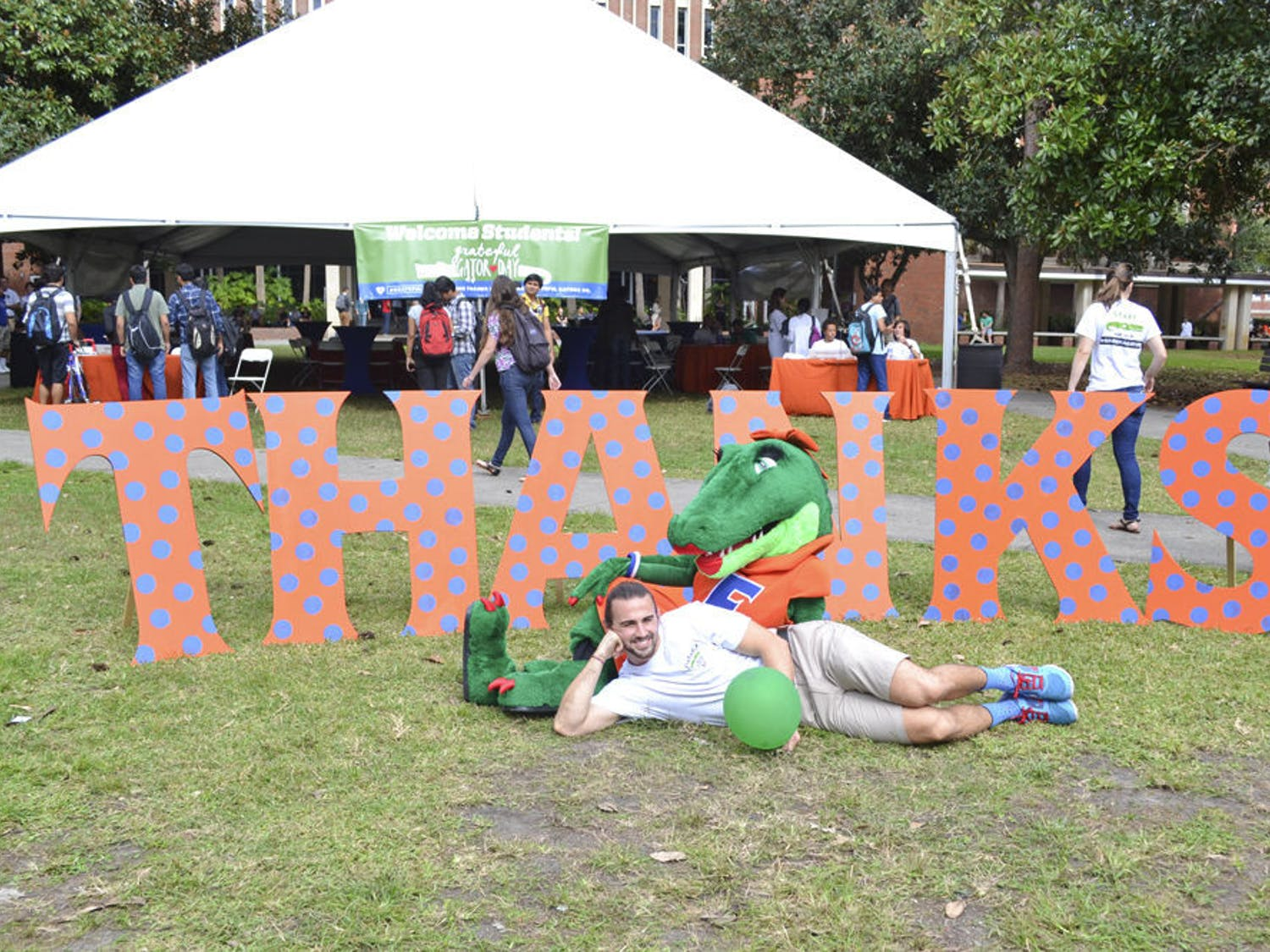 """It was the week before Thanksgiving, but several hundred UF students gave thanks Wednesday morning during the first-ever Grateful Gator Day. Students thanked about 30,000 UF donors on the Plaza of the Americas by writing about 1,000 handwritten orange cards, video-taping their Gator Chomps and posing for photos with a giant, polka-dotted """"THANKS."""" The event served to make students aware of how much money people donate to the university, said Kevin Marfiak, a 23-year-old UF biology senior and Cicerone who helped plan the event."""