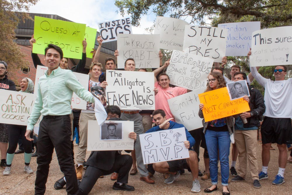 """<p dir=""""ltr""""><span>Anthony Rojas (front), a 21-year-old third-year political science major who organized the protest against student body president Smith Myers, tries to speak to a crowd while counter-protesters hold signs behind him and other protesters.</span></p><p><span></span></p>"""