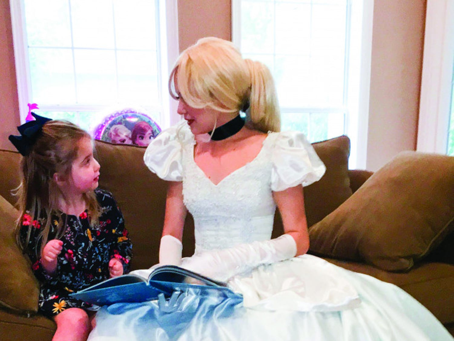Dressed as Cinderella, Kailyn Allen, a 22-year-old UF law student, reads a book to 4-year-old Phoebe Dooley. Dooley was diagnosed with a terminal brain tumor in March 2016.