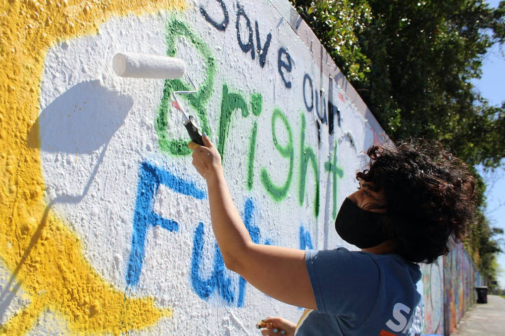 <p>Alondra Arce, 20, a UF sustainability sophomore, paints a mural that says &quot;Save Our Bright Futures&quot; on Sunday, March 7, 2021. Arce recruited student volunteers to help her create the mural along 34th Street in Gainesville to raise awareness about Senate Bill 86, which would limit some students&#x27; access to state funding for college if passed.</p><p><br/></p>